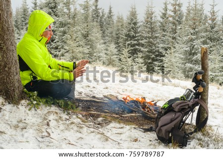 A traveler warming his hands at the fire during the winter hike in the mountains