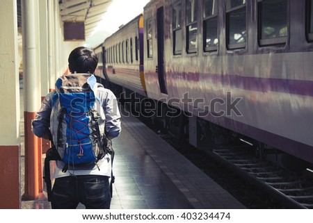 A traveler with backpack in the railway. vintage effected photo.