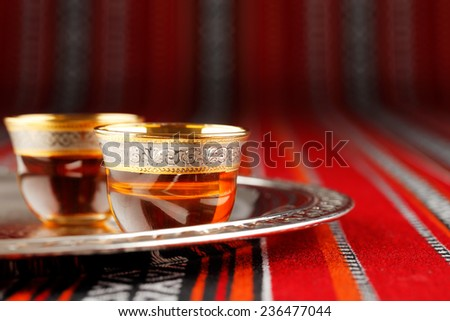 A tray of Arabian tea cups is placed on Arabian woven fabric. Tea symbolise Arabian hospitality  - stock photo