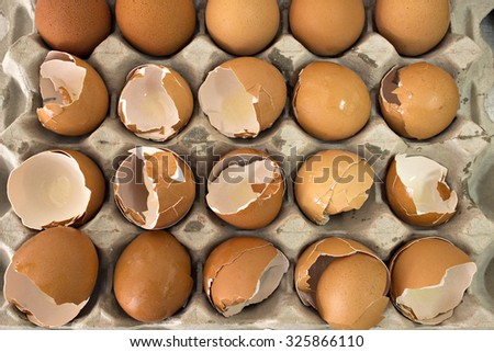 A tray of eggs, the majority of them broken. - stock photo