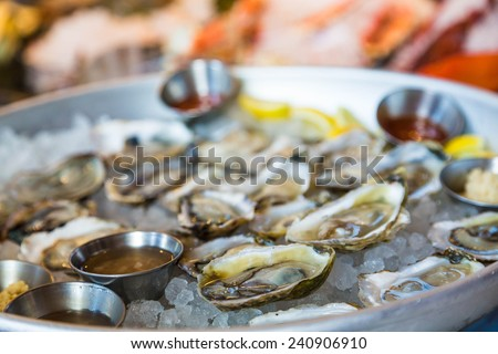 A tray of fresh oysters on the half shell on ice with sauce - stock photo