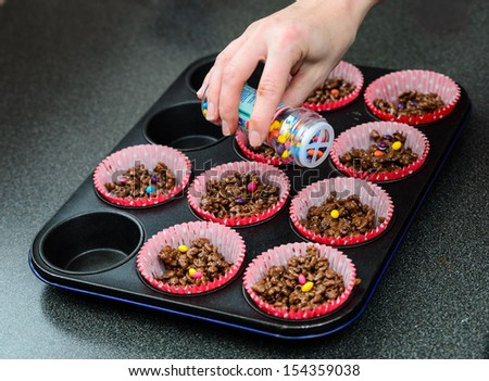 A tray of freshly made chocolate crispies with coloured topping being sprinkled on - stock photo