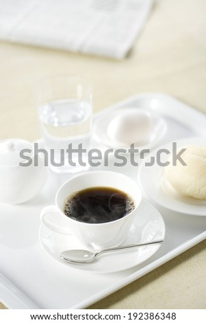 A tray with coffee and some food on a table. - stock photo