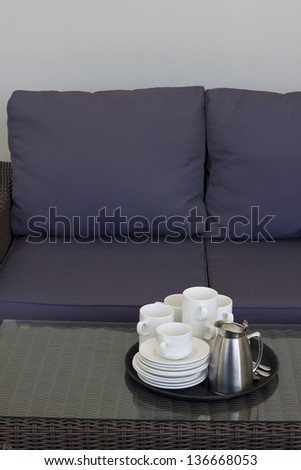 A tray with empty coffee cups and a full coffee pot and sugar bowl placed on a rattan table with a glass top, in front of a rattan sofa with blue cushions