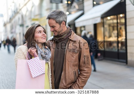 A trendy couple is standing arm in arm in the city center. They are in a cobbled car-free street. The woman is wearing a yellow shirt and pink shopping bags and the grey hair man has a leather coat - stock photo