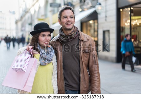 A trendy couple is walking arm in arm in the city center. They are in a cobbled car-free street. The woman is wearing a black hat and pink shopping bags and the grey hair man has a leather coat - stock photo