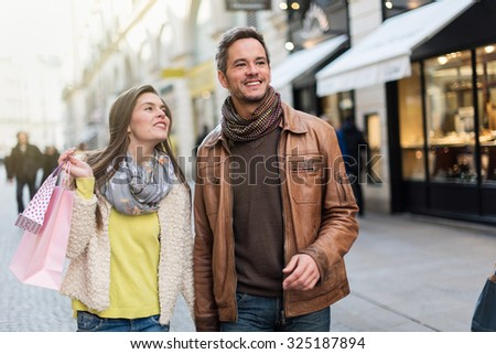 A trendy couple is walking in the city center. They are in a cobbled car-free street. The woman is wearing a yellow shirt and pink shopping bags and the grey hair man with beard has a leather coat - stock photo