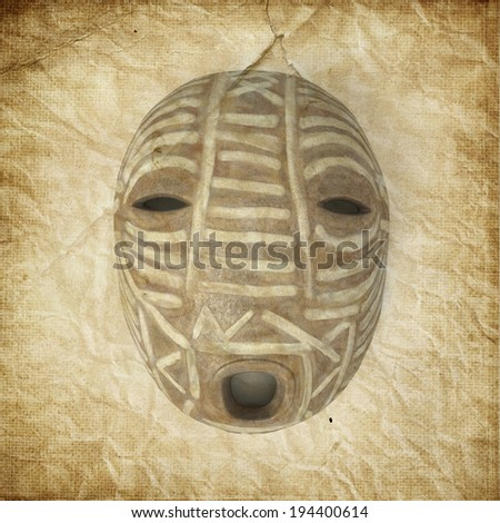 A tribal mask from Africa on old paper background - stock photo