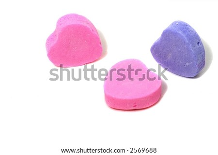 A trio of candy hearts on a white background