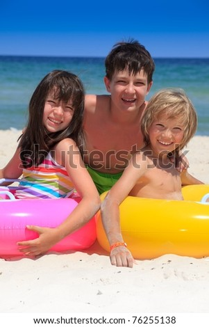 A trio of happy kids on the beach. - stock photo