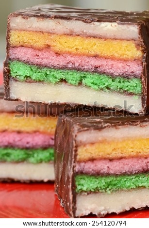 A trio of petit fours layered with marzipan and colorful cake - stock photo