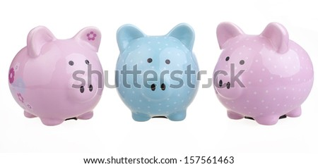 A trio of piggy banks lined up next to each other on white background.