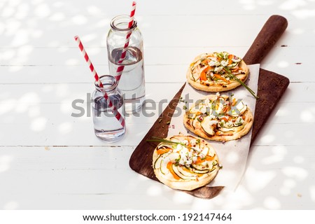 A trio of tasty mini vegetarian pizzas with eggplant, bell pepper, cheese and herbs served on a long wooden board with glass jars of fresh water - stock photo