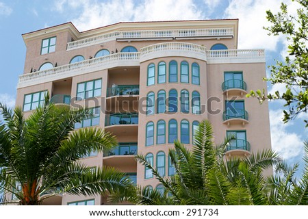 A tropical, art deco style condo with a bright blue sky and palm trees.