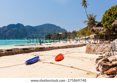 a tropical beach in thailand with straw umbrellas and a vibrant exotic sea - stock photo
