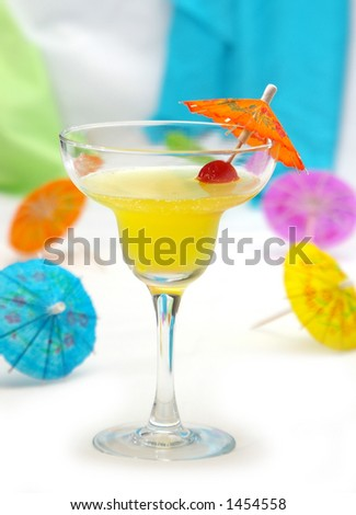 A tropical drink surrounded by cocktail umbrellas. - stock photo