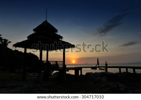 a tropical-style pavilion by the beach on an island in the Gulf of Thailand during sunset - stock photo