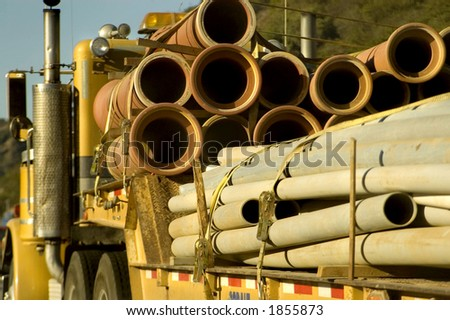 A truck hauls pipes. - stock photo