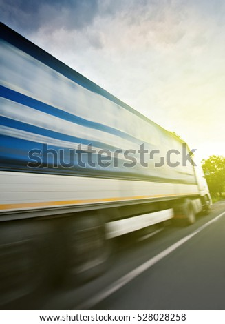 A truck in high speed as seen from lateral side driwing on highway toward sunny speedy delivery