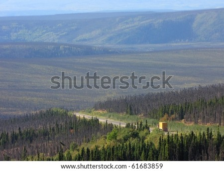 A truck on the Dalton highway: the road through Alaskan wilderness - stock photo
