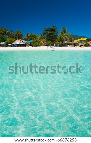 A truly white sand beach and crystal clear water resembling a swimming pool on the island paradise of Ko Lipe, Thailand - stock photo
