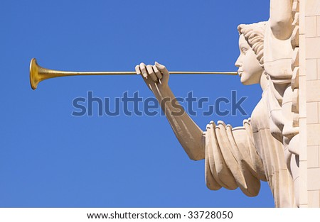A trumpeting golden music angel statue detail over blue sky. - stock photo