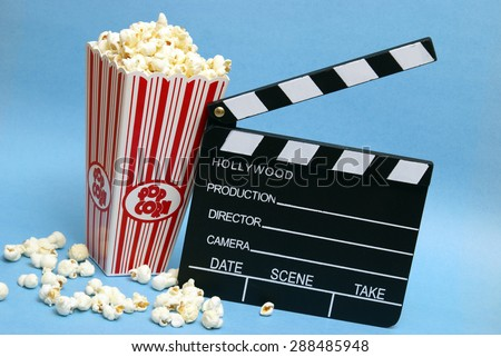 A tub of popcorn and a clapboard to represent the movie industry. - stock photo