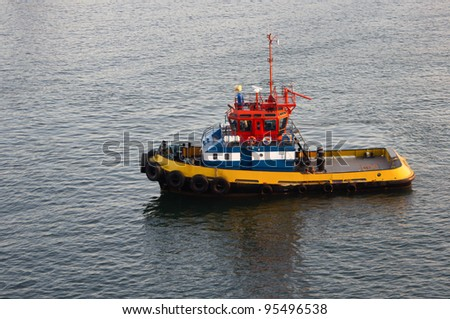 A tug boat waiting to assist ships in the harbor - stock photo