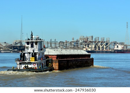 A Tugboat pushes a barge down the Mississippi River at New Orleans. - stock photo