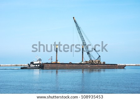 A tugboat pushes a floating crane on a barge and other repair equipment and materials toward the breakwall between the open waters of Lake Erie and the harbor at Cleveland, Ohio