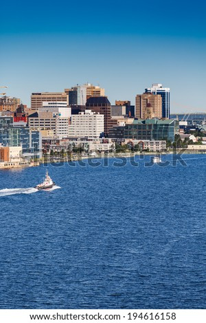 A tugboat sailing past the city of Halifax, Nova Scotia in blue water - stock photo