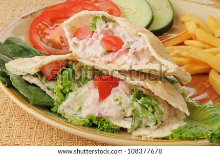 A tuna pita sandwich wiht tomatoes and fries