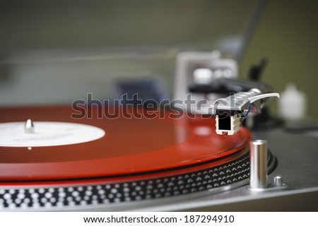a turntable with a red record. - stock photo