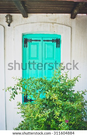 A turquoise wooden shutter in a greek house - stock photo