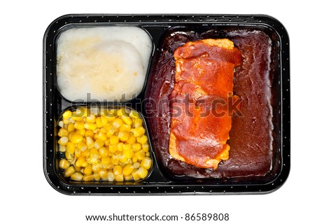A TV dinner consisting of ribs, mashed potatoes and corn isolated on white