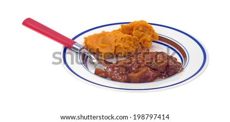 A TV dinner of braised beef in a red chili sauce with mashed sweet potatoes on a plate with fork. - stock photo