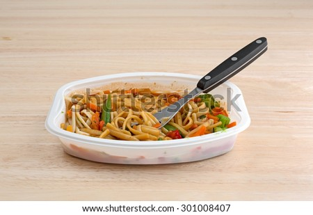 A TV dinner of noodles and vegetables in a white tray with a fork on a wood table top.