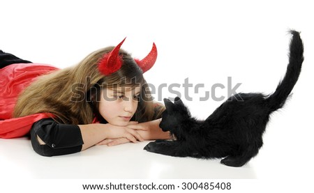 "A tween ""devil"" staring eye-to-eye with a big black Halloween cat.  Isolated on white."
