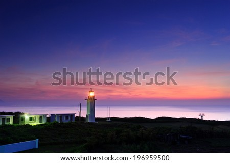 A twilight scene of a lighthouse and outbuildings by the sea.