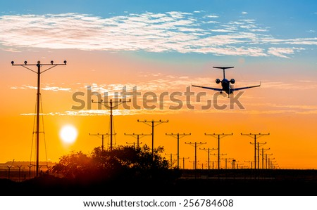 A twin engine commercial jet preparing for landing during sunset with landing lights lit. - stock photo