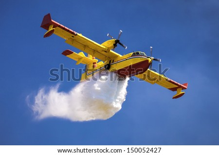 A twin-engined water bomber dumping its load