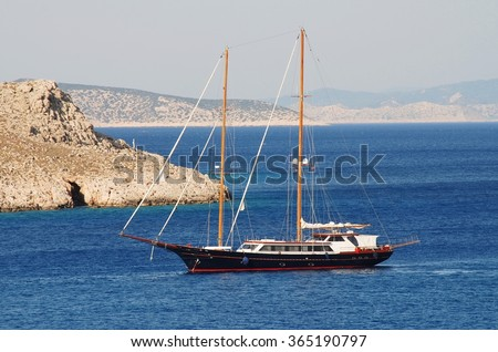 A twin masted sailing boat enters the harbour at Emborio on the Greek island of Halki.