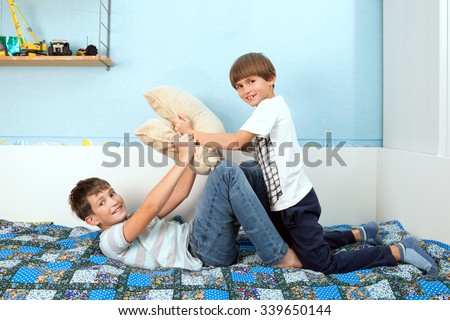 a two boys is fighting by pillows in bedroom