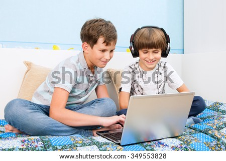 A two brothers is playing on laptop in home - stock photo