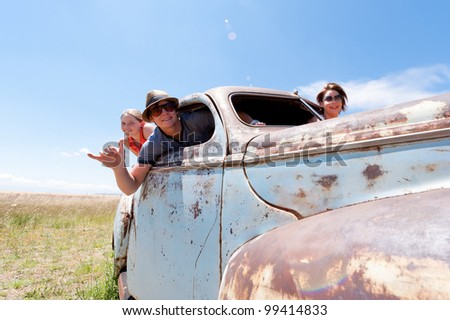 a two girls and guy in old rusty car