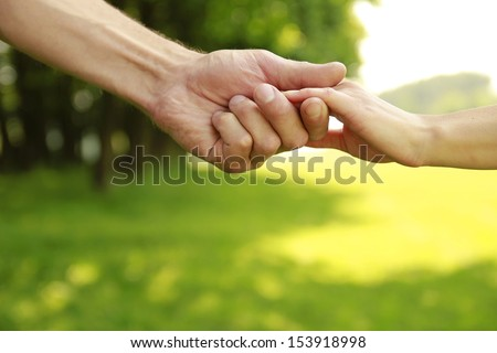 a two hands of a loving couple on nature