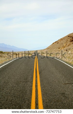 a two lane highway stretches for miles and miles in the hot summer sun of Death Valley California