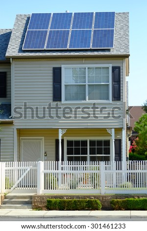 A two story residence has used available roof space to mount solar panels to defray utility company  electrical charges.