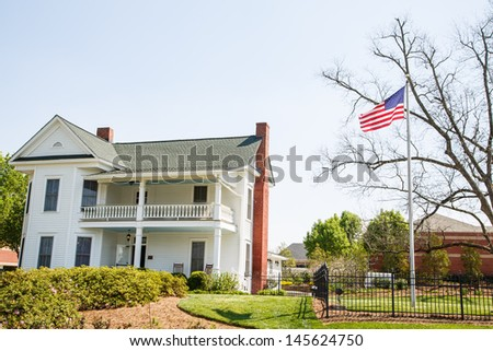 A two story traditional white farmhouse with an American flag