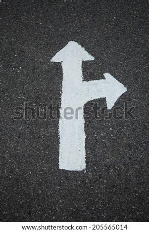 A two way arrow symbol on a black asphalt road surface. - stock photo